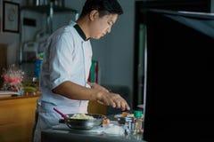 Cozinheiro chefe que cozinha em um restaurante imagens de stock royalty free