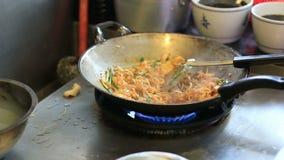 Cozinheiro chefe que cozinha macarronetes de arroz salteado tailandeses da almofada na bandeja grande video estoque