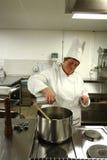 Cozinheiro chefe que cozinha na cozinha foto de stock