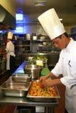 Cozinheiro chefe que cozinha na cozinha Fotografia de Stock Royalty Free