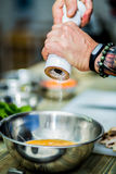 Cozinheiro chefe que cozinha na cozinha que faz o alimento saudável com vegetais fotografia de stock