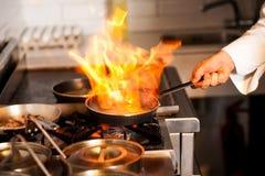 Cozinheiro chefe que cozinha no fogão de cozinha foto de stock royalty free