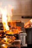 Cozinheiro chefe que cozinha no fogão de cozinha Foto de Stock