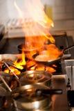 Cozinheiro chefe que cozinha no fogão de cozinha Imagens de Stock
