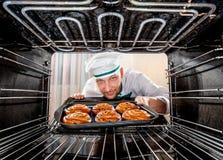Cozinheiro chefe que cozinha no forno foto de stock
