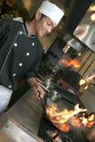 Cozinheiro chefe que cozinha no jantar Imagem de Stock Royalty Free