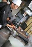Cozinheiro chefe que cozinha no jantar Fotos de Stock