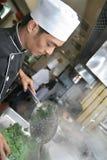 Cozinheiro chefe que cozinha no jantar Imagens de Stock Royalty Free