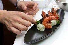 Cozinheiro chefe que cozinha o menu Pan Fried Tiger Prawn com pepino encaracolado fotos de stock royalty free