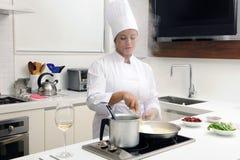 Cozinheiro chefe que cozinha o stirring do risotto Fotografia de Stock Royalty Free