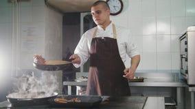 Cozinheiro chefe que cozinha os espaguetes no restaurante - ingredientes de mistura filme