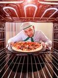 Cozinheiro chefe que cozinha a pizza no forno fotografia de stock royalty free