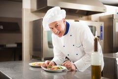 Cozinheiro chefe que decora um prato Imagem de Stock Royalty Free