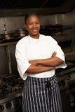 Cozinheiro chefe que está ao lado do fogão na cozinha fotografia de stock