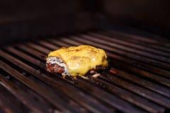 Cozinheiro chefe que faz o hamburguer Cozinhando o Hamburger Costoleta da carne ou da carne de porco com o queijo que grelha na g imagem de stock