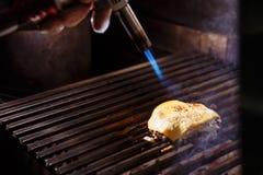 Cozinheiro chefe que faz o hamburguer O cozinheiro derrete o queijo em um hamburguer O cozinheiro usa uma tocha de sopro para der imagem de stock