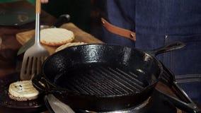 Cozinheiro chefe que frita rissóis da carne da carne com queijo para Hamburger e cheeseburgers Metragem conservada em estoque O c video estoque