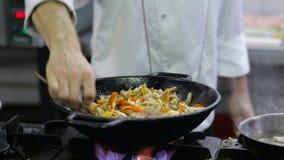 Cozinheiro chefe que frita vegetais e carne em um frigideira chinesa na cozinha filme