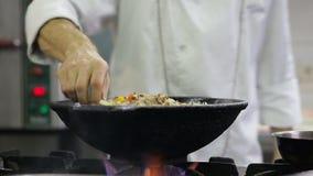 Cozinheiro chefe que frita vegetais e carne em um frigideira chinesa na cozinha vídeos de arquivo