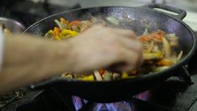 Cozinheiro chefe que frita vegetais e carne em um frigideira chinesa na cozinha video estoque