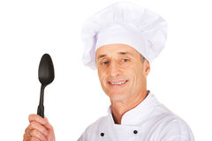 Cozinheiro chefe que guarda a colher plástica preta Fotografia de Stock