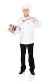 Cozinheiro chefe que guarda o potenciômetro de aço inoxidável e a colher Fotografia de Stock