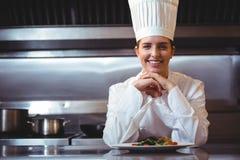 Cozinheiro chefe que inclina-se no contador com um prato imagens de stock