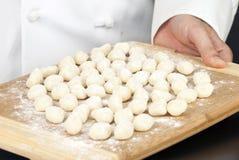 Cozinheiro chefe que indica Gnocchi na placa de estaca Fotos de Stock