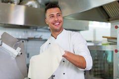 Cozinheiro chefe que lanç a massa da pizza Foto de Stock Royalty Free