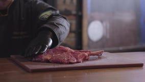 Cozinheiro chefe que lubrifica a parte fresca crua de reforços da carne postos de conserva e prontos para ser fritado na grade ap vídeos de arquivo