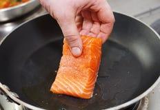 Cozinheiro chefe que põr a faixa salmon sobre a bandeja quente Fotografia de Stock