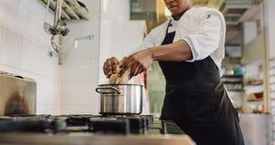 Cozinheiro chefe que prepara o alimento na cozinha do restaurante fotografia de stock