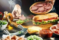Cozinheiro chefe que prepara sanduíches frescos saborosos do baguette fotos de stock royalty free