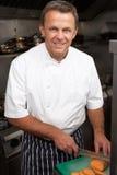 Cozinheiro chefe que prepara vegetais na cozinha do restaurante fotografia de stock royalty free