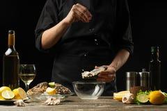 Cozinheiro chefe que salga a ostra com o limão no fundo do vinho seco em um fundo escuro, foto horizontal, menu, restaurante, ita imagens de stock