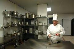 Cozinheiro chefe que sharpening as facas Foto de Stock Royalty Free