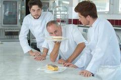 Cozinheiro chefe que verifica bolos dos assistentes imagens de stock