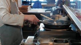 Cozinheiro chefe Is Stirring Vegetables com carne no frigideira chinesa na cozinha comercial filme