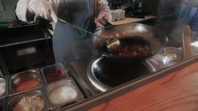 Cozinheiro chefe Is Stirring Vegetables com carne no frigideira chinesa na cozinha comercial, culinária pan-asiático vídeos de arquivo