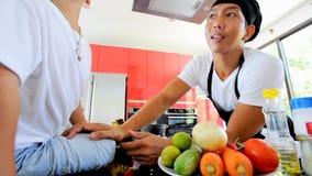 Cozinheiro chefe tailandês privado que cozinha, seu filho pequeno no assento próximo do chapéu do ` s do cozinheiro chefe na tabe vídeos de arquivo