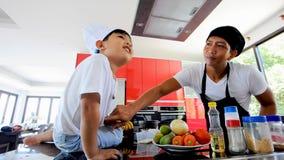 Cozinheiro chefe tailandês que cozinha, seu filho pequeno no assento próximo do chapéu do ` s do cozinheiro chefe na tabela em um filme