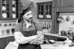 Cozinheiro chefe tattooed pensativo que mantém os braços na posição cruzada imagens de stock