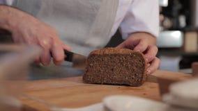 Cozinheiro Cuts uma fatia de pão em uma placa de corte com uma faca filme