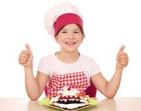 Cozinheiro da menina com crepes e polegares acima Imagem de Stock Royalty Free