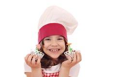 Cozinheiro da menina com o queque da flor da mola Foto de Stock