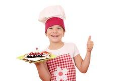 Cozinheiro da menina com os crepes na placa e no polegar acima Foto de Stock
