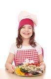 Cozinheiro da menina com peixes da truta Imagens de Stock Royalty Free