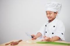 Cozinheiro da menina, cozinheiro chefe das crianças receoso dos vegetais Fotos de Stock Royalty Free