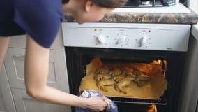 Cozinheiro da mulher da dona de casa e forno da verificação com as asas de galinha roasted na cozinha em casa filme