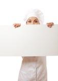 Cozinheiro da mulher que olha sobre o quadro de avisos de papel do sinal. Fotos de Stock Royalty Free